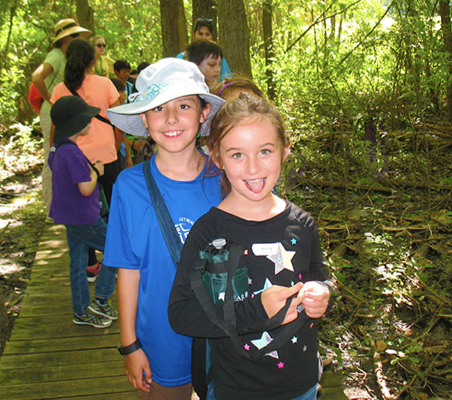 Two friends posing for a picture in the woods at camp