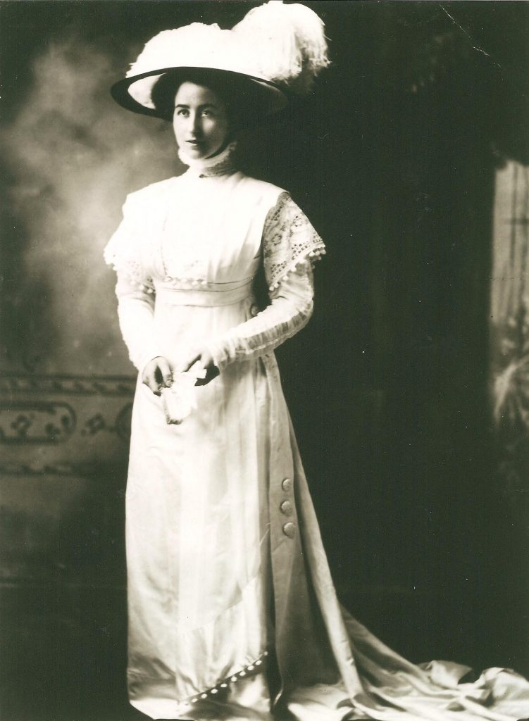 Bessie Heard Portrait in a white gown wearing a large hat with a big feather on top