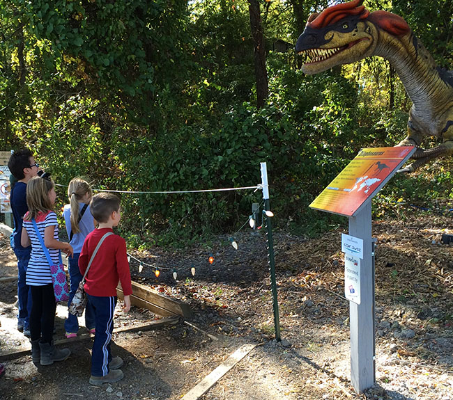 Children staring at a dinosaur that spits water