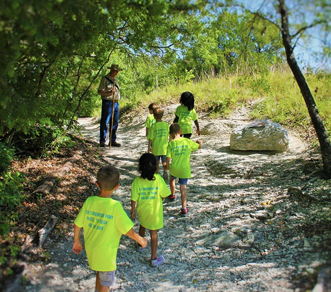 Six children from summer camp on a guided tour with a trail guide