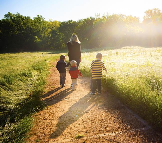 A family walks through the beautiful trail at Heard around dawn