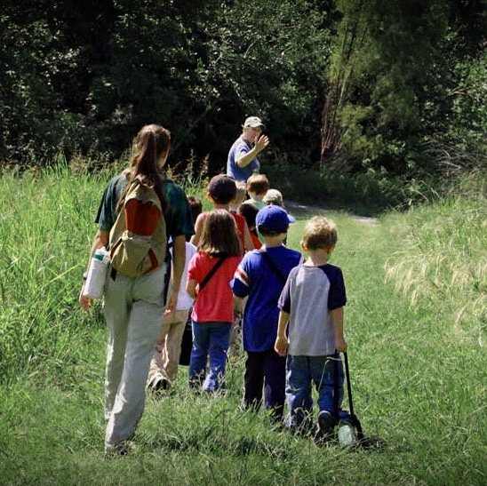 Kids walking the trail with a camp leader during spring break mini camp